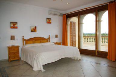 Schlafzimmer mit Doppelbett und Zugang auf Balkon