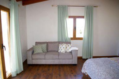 Gemütliche Couch im offenen Schlafzimmer